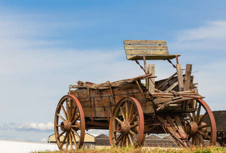 Old wooden brocken cart in the field. Selective focus, close up, street photo, travel photo. Imagens