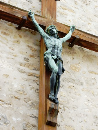 Green sculpture of Jesus on a wood croos on a wall photo