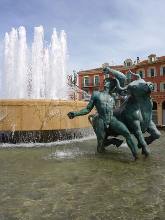 Statue of the fountain and colored buildings at the place Massena, Nice, France photo