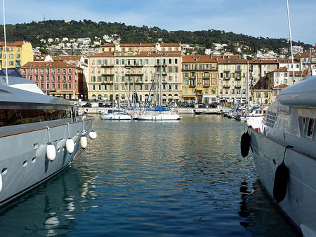 View of the old port of Nice, France, between two big yachts and by beautiful weather photo