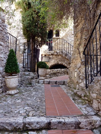 Red pavement, stairs with fences and walls of houses in a street of historical Eze village in south France photo