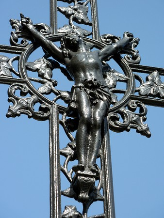 Jesus cross made of black metal with lots of decorations around and blue sky behind Stock Photo - 7116848