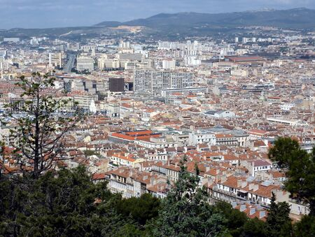 Aerial view of Marseilles city with all the colored roofs of the buildings and the mountain behind, France photo