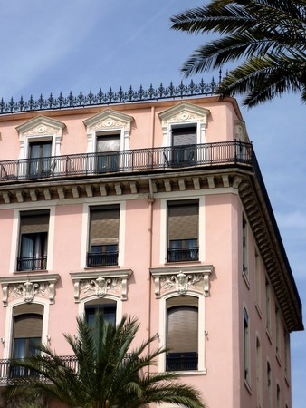 pal: Pink old building at Nice, France, and leaves of two pal trees by beautiful weather Stock Photo