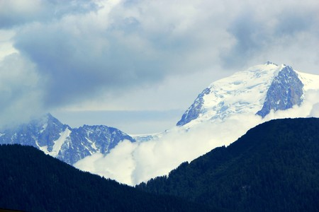 Snowy mountain high in the Alps behind fir trees forest by cloudy weather Stock Photo - 7532844
