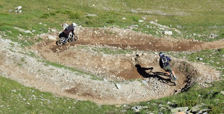 sports programme: Two equipided bikers riding their VTT bike in the mountain