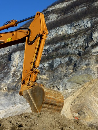 buildingsite: Orange mechanical digger arm next to a mountain Stock Photo