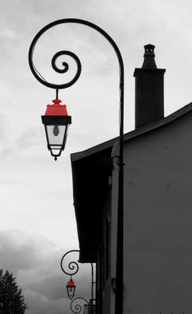 Old red lamps of old buildings in a street by cloudy weather photo