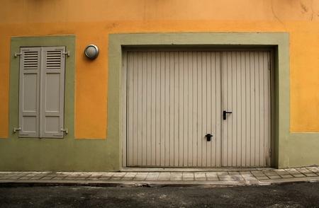 garage door: Closed garage door and window with closed shutters in a pink facade in a street