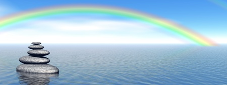Balanced grey stones in the deep blue ocean with a beautiful rainbow Stock Photo