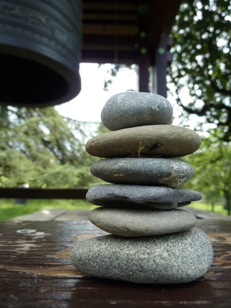 horizontals: Zen stones on a peace of wood next to a japonese bell in a park