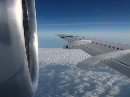 Flying plane wing and motor upon clouds in a deep blue sky
