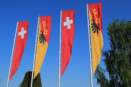 Swiss and Geneva canton flags moving in the wind and deep blue sky photo