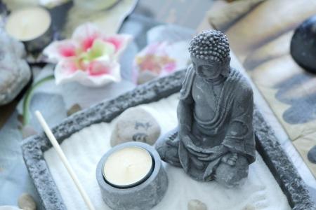 Grijze steen Boeddha in de voorkant van een kleine gele kaars op een zen tafel Stockfoto