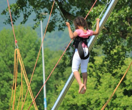 Young girl playing at a rope jumping game in nature background