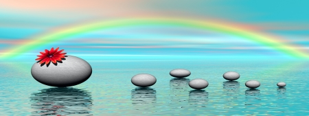 A big grey stones with a beautiful red flower on it and small pebbles upon ocean and with colored sky with rainbow