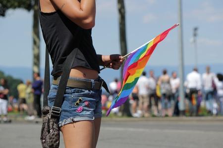 transexual: GINEBRA, Suiza - 02 de julio: Una mujer no identificada con una bandera del arco iris mientras participaba en el desfile del Orgullo Gay 2011 para apoyar los derechos de los homosexuales, el 2 de julio de 2011 en Ginebra, Suiza.