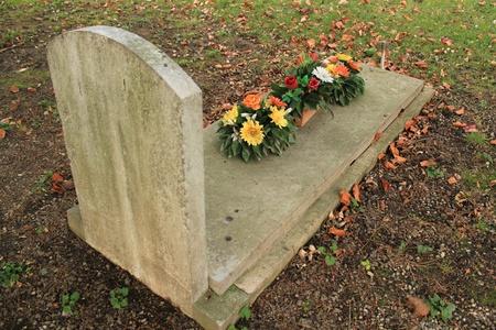Tomb bedekt met gekleurde bloemen met de herfst gekleurde rode bladeren in een begraafplaats Stockfoto