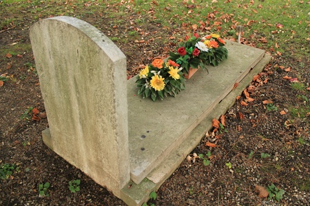 headstone: Tomb covered with colored flowers with autumn colored red leaves in a cemetery Stock Photo