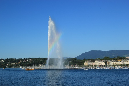 geneva: View of Geneva city, Switzerland. A beautiful rainbow colors the mist on the 140 m water fountain on Geneva Lake. It is the symbol of this swiss city and is called the Jet D Editorial