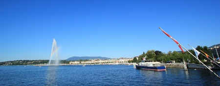 Panorama of Geneva city, Switzerland. A beautiful rainbow colors the mist on the 140 m water fountain on Geneva Lake. It is the symbol of this swiss city and is called the Jet D