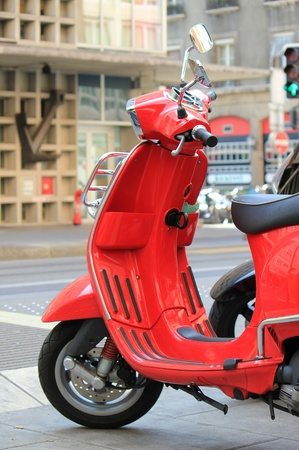 Red scooter parked in the city street photo