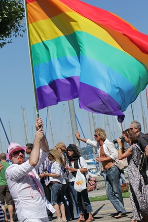Man holding a big rainbow flag while taking part in Gay Pride Parade, Geneva, Switzerland.