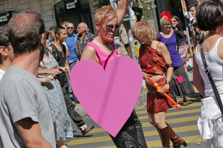 Young woman wearing pink clothes and a big heart while marching at the Gay Pride 2011, Geneva, Switzerland