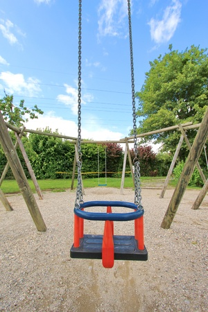 reminisce: Blue and red swing in a park playground, waiting for the next child. Stock Photo