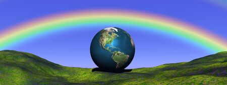 Earth planet on a green grass hill and under a beautiful rainbow photo