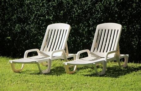 Two white lawn chairs in a green garden by summer Stock Photo