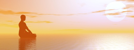 Man meditating upon the ocean by beautiful hazy sunset Stock Photo