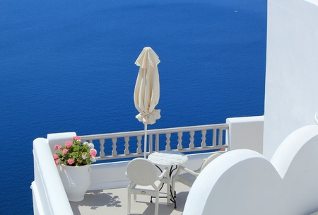 Umbrella, flowers, chairs and table in a white balcony at the sea, Santorini, Greece photo