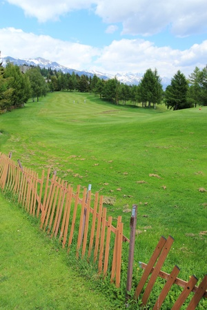 Golf course and fence by summer, Crans Montana, Switzerland  photo