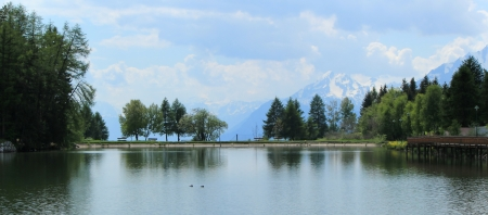 Long lake, trees and mountain by summer, Cran Montana, Switzerland photo