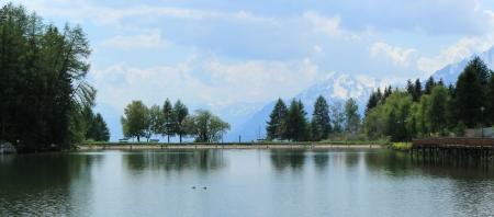 long lake: Long lake, trees and mountain by summer, Cran Montana, Switzerland Stock Photo