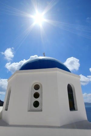 Blue dome and cross under of a greek orthodox church under the sun in Santorini island, Greece, by beautiful weather photo