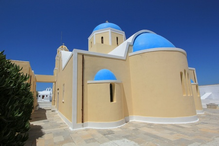 Blue dome and yellow walls  of a greek orthodox church in Santorini island, Greece, by beautiful weather photo