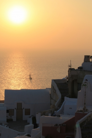 Beautiful sunset and boat at Oia village, Santorini, Greece photo