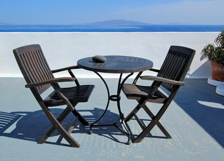 View on islands and Aegean sea from a balcony with tow black chairs and table made of wood at Oia, Santorini island, Greece photo