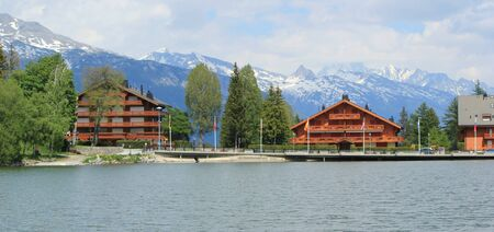 long lake: Swiss chalet, Long lake and Alps mountains in summer, Crans Montana, Switzerland