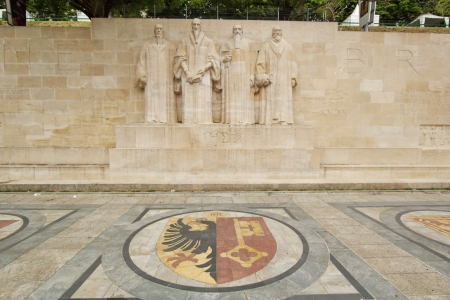 protestant: Sculptures of the four great figures of the geneva protestant movement : Guillaume Farel (1489 - 1565), Jean Calvin (1509-1564), Theodore de Beze (1513-1605) and John Knox (1513-1572) on the reformation wall in Bastions park in front of Geneva flag on the