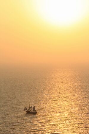 Small old sailing boat on the ocean by beautiful sunset photo