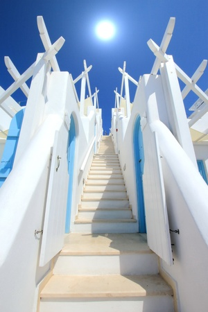 Beautiful colorful stairs with two walls going to the sun in deep blue sky photo