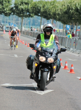 GENEVA, SWITZERLAND - JULY 22   security motorbike running before unidentified males cyclists at the International Geneva Triathlon, on July 22, 2012 in Geneva, Switzerland