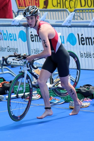 GENEVA, SWITZERLAND - JULY 22   unidentified athlet holding his bike at transition space at the International Geneva Triathlon, on July 22, 2012 in Geneva, Switzerland  Stock Photo - 14638810
