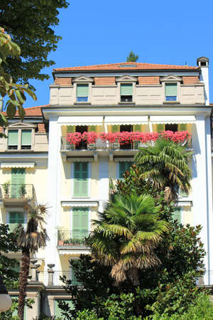 Facade of a building with flowers and palm trees in front of it by summer, Lugano, Switzerland photo