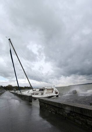 Ran aground boat during big storm by cloudy and rainy day in Geneva, Switzerland photo