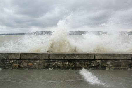 Big wave upon the wall of the lakeside in Geneva, Switzerland photo