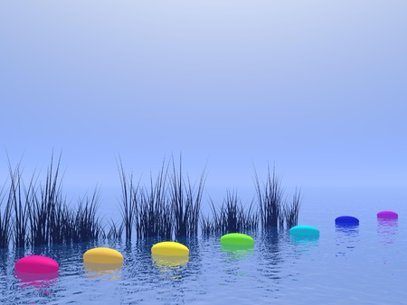 Seven pebbles with chakras colors upon the deep blue ocean and in front of vegetation photo